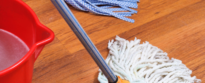 mopping of wood floors by two mops and red bucket